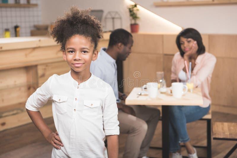 menina afro adorável no café com seus pais borrados imagem de stock royalty free
