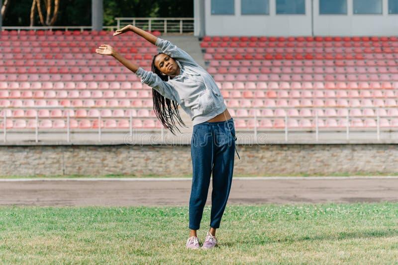 A menina afro-americana atlética está escutando a música nos fones de ouvido ao fazer dar certo exercícios no estádio imagem de stock royalty free