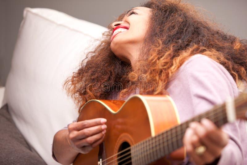 Menina afro-americana bonita que joga a guitarra imagens de stock royalty free