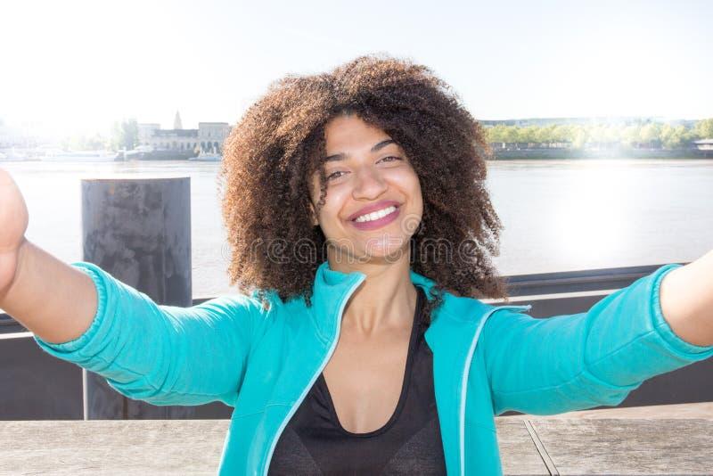 A menina afro-americana do turista faz o selfie com smartphone fotos de stock