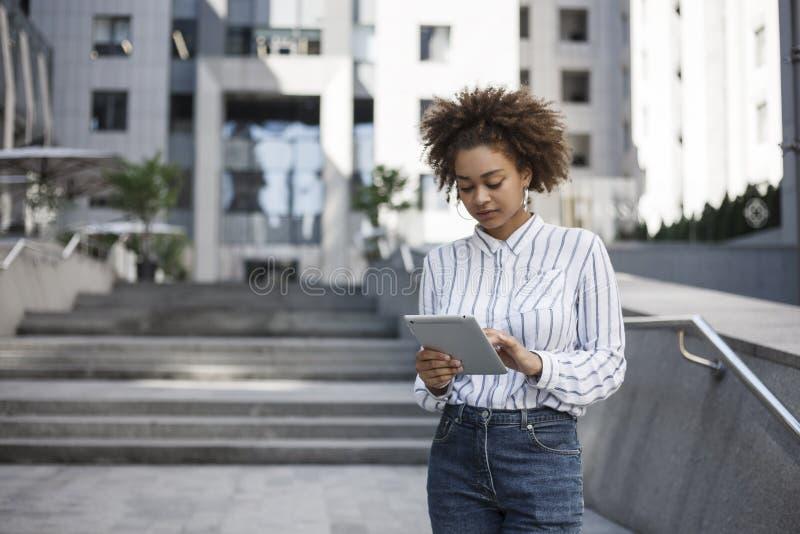 A menina afro-americana está estando na rua perto do prédio de escritórios Trabalha em uma tabuleta fotos de stock