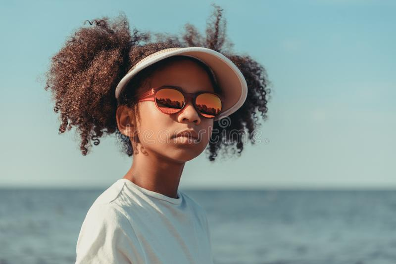 menina afro-americano bonita no tampão e nos óculos de sol que olham ausentes ao estar fotografia de stock royalty free