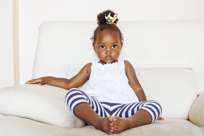 A menina afro-americano bonita pequena que senta-se na coroa vestindo do brinquedo da cadeira branca na cabeça gosta da princesa  foto de stock royalty free