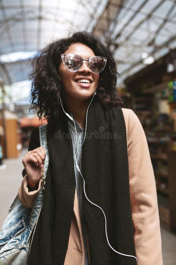 Menina afro-americano bonita que está na rua nos fones de ouvido Retrato da menina fresca com cabelo encaracolado escuro dentro imagens de stock royalty free