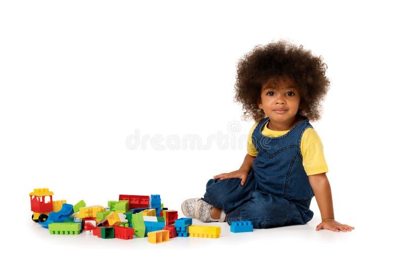 Menina afro-americano bonito pequena bonita no assoalho com os lotes de blocos plásticos coloridos no estúdio, isolados imagem de stock