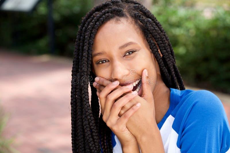 Menina afro-americano bonito que ri com as mãos que cobrem a boca fotos de stock