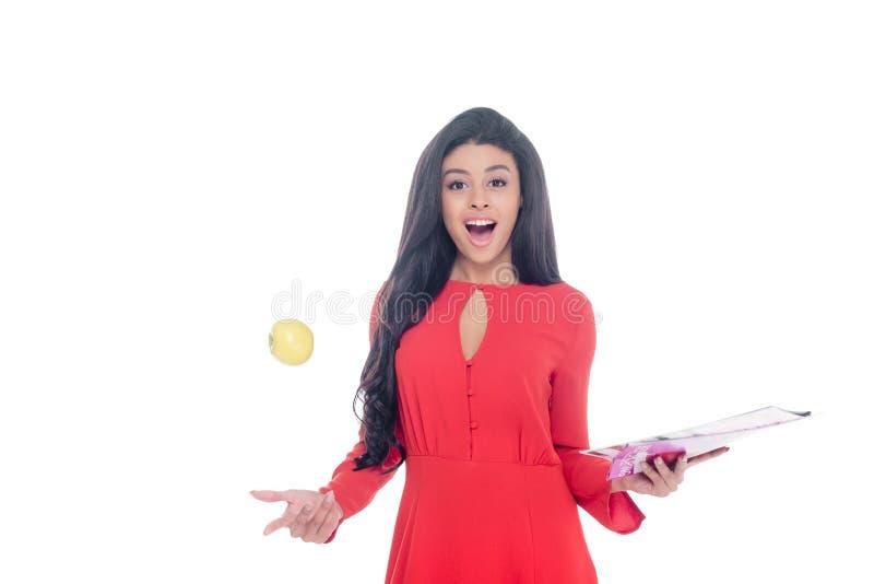menina afro-americano chocada no vestido vermelho que guarda o compartimento e que joga a maçã isolada imagem de stock royalty free