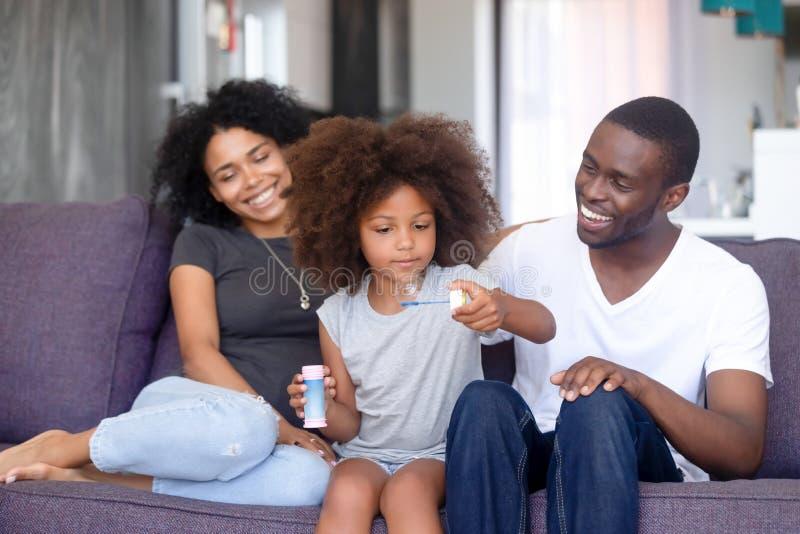 Menina afro-americano com os pais que jogam com bolha de sabão foto de stock
