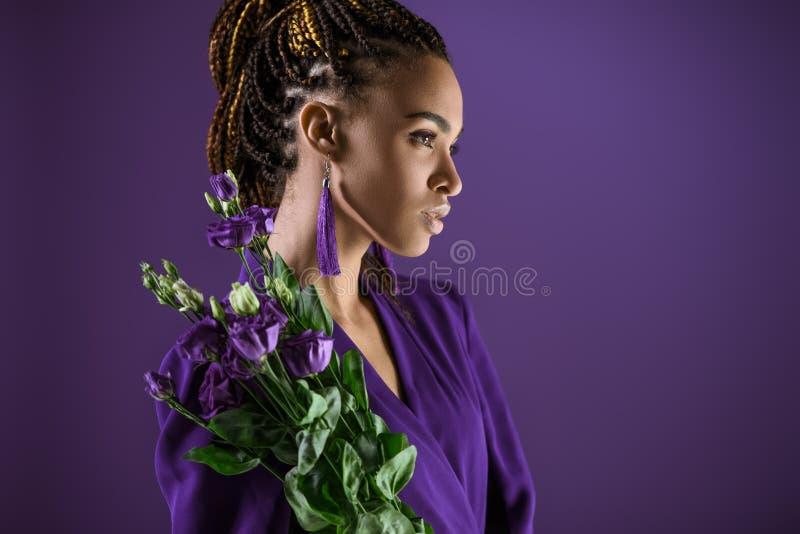 A menina afro-americano elegante que levanta com eustoma roxo floresce, imagem de stock royalty free