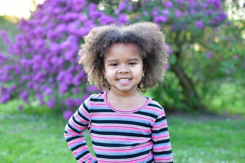 Menina afro-americano encaracolado só que levanta em um parque com flores e sorrisos fotos de stock