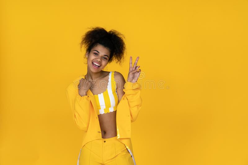 A menina afro-americano feliz veste a roupa amarela à moda isolada no fundo foto de stock
