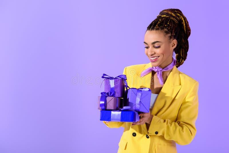 menina afro-americano no terno amarelo que guarda presentes roxos, em na moda ultra fotos de stock