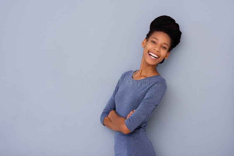 Menina afro-americano nova bonito que ri contra o fundo cinzento com os braços cruzados imagem de stock