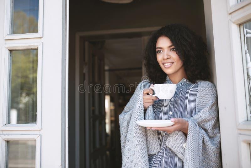 Menina afro-americano nova com o café bebendo escuro do cabelo encaracolado que inclina-se na porta Senhora bonita que está com c imagens de stock