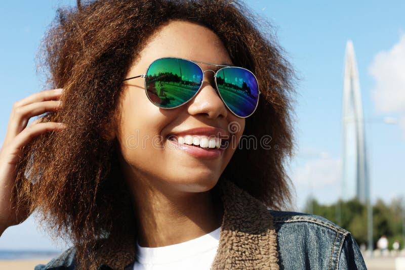 A menina afro-americano nova nos óculos de sol, levantando fora, vestiu ocasional, com cabelo volumoso curto imagem de stock royalty free