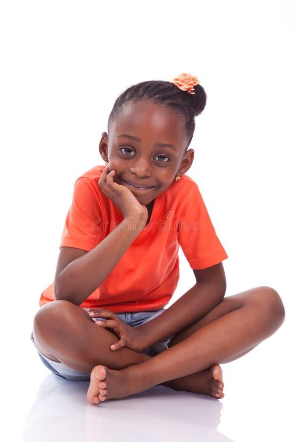 Menina afro-americano pequena bonito que senta-se no assoalho - c preto fotografia de stock