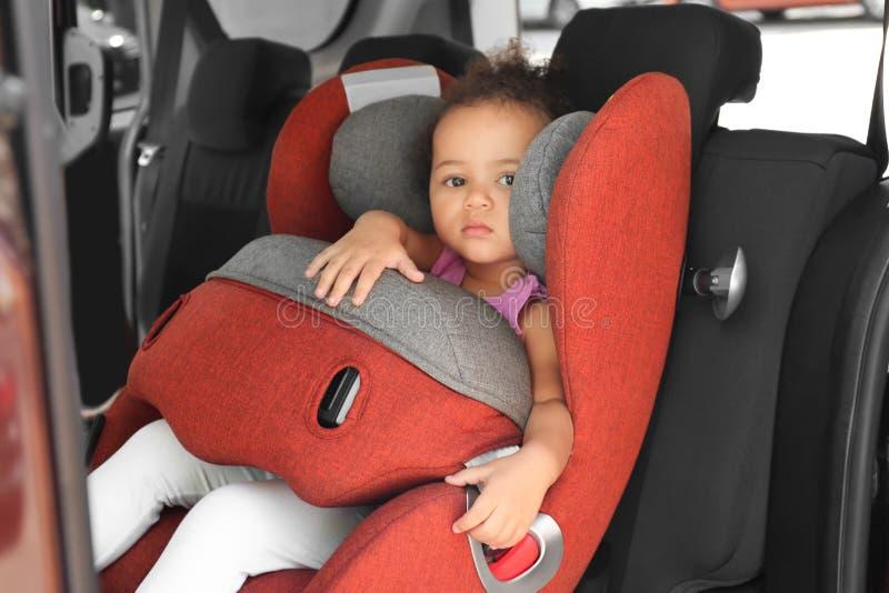 Menina afro-americano pequena no assento da segurança da criança para dentro imagens de stock royalty free