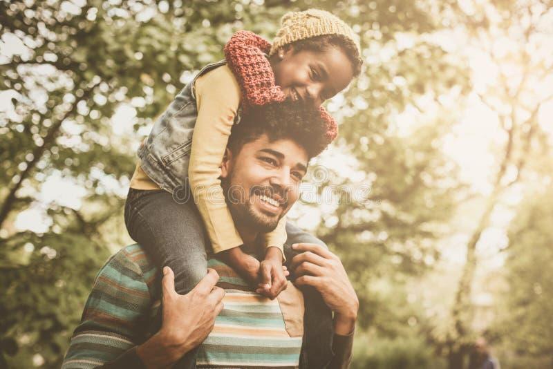 Menina afro-americano que senta-se em ombros do pai e em e fotografia de stock