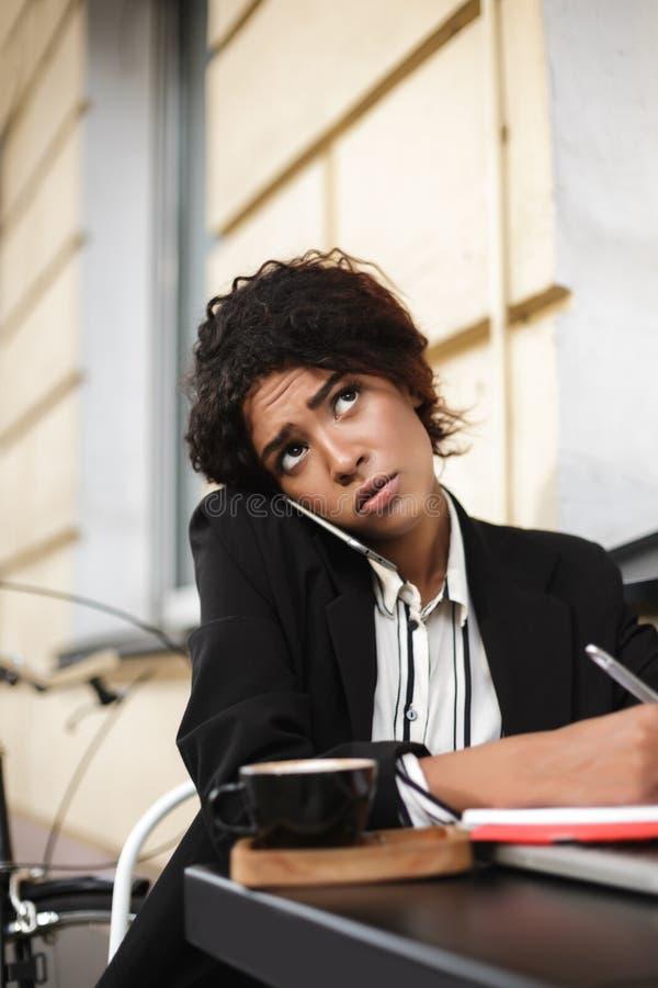 Menina afro-americano que senta-se na tabela do café e que fala em seu telefone celular ao tiredly olhar de lado Pensativo imagens de stock royalty free