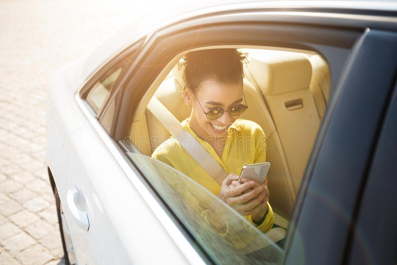 Menina afro-americano que texting no telefone, sentando-se no carro fotos de stock