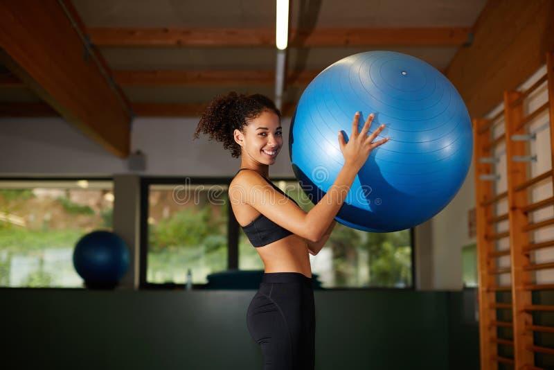Menina afro atrativa com cabelo encaracolado que sorri no gym foto de stock
