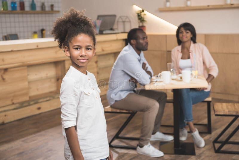 menina afro bonita no café com seus pais borrados foto de stock