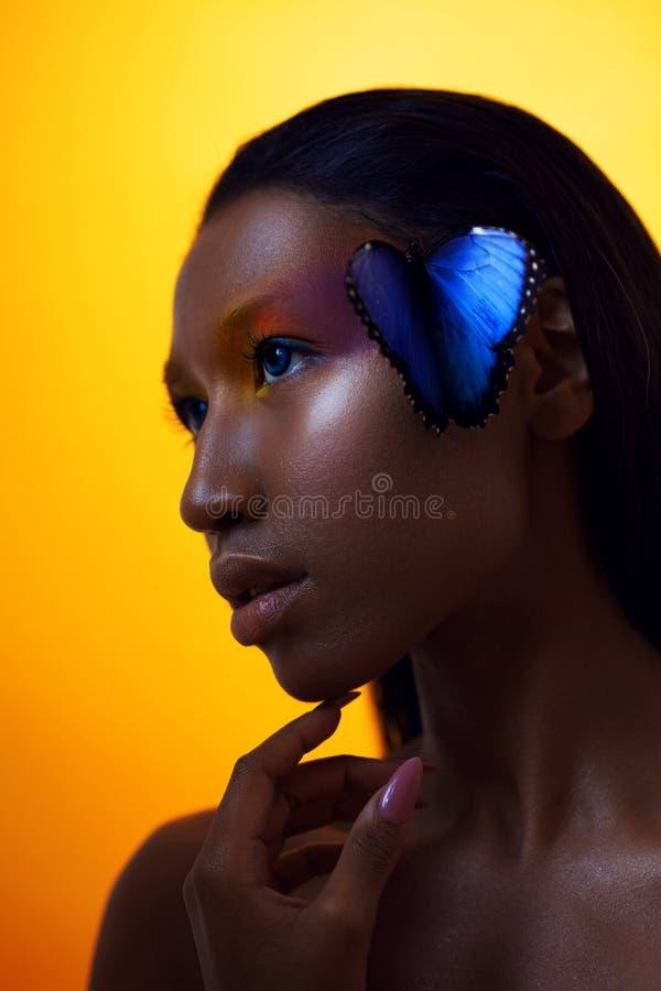 Menina afro bonita nova, com borboleta azul, retrato da beleza no fundo amarelo fotos de stock royalty free