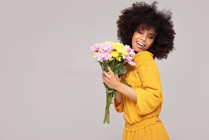 Menina afro bonita nova com flores foto de stock