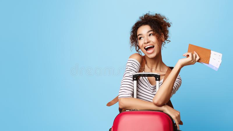 Menina afro extático que guarda bilhetes e que olha de lado fotografia de stock