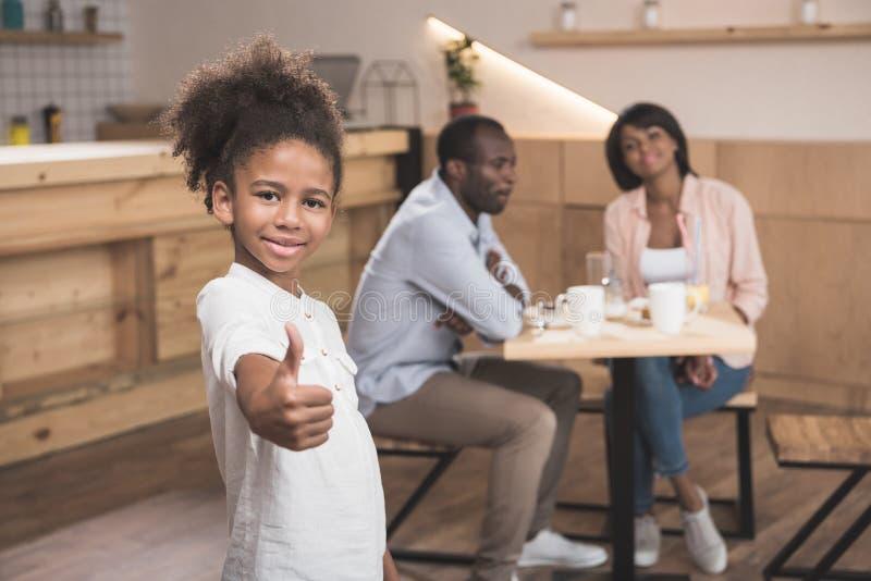 menina afro que mostra o polegar acima com seus pais borrados imagens de stock