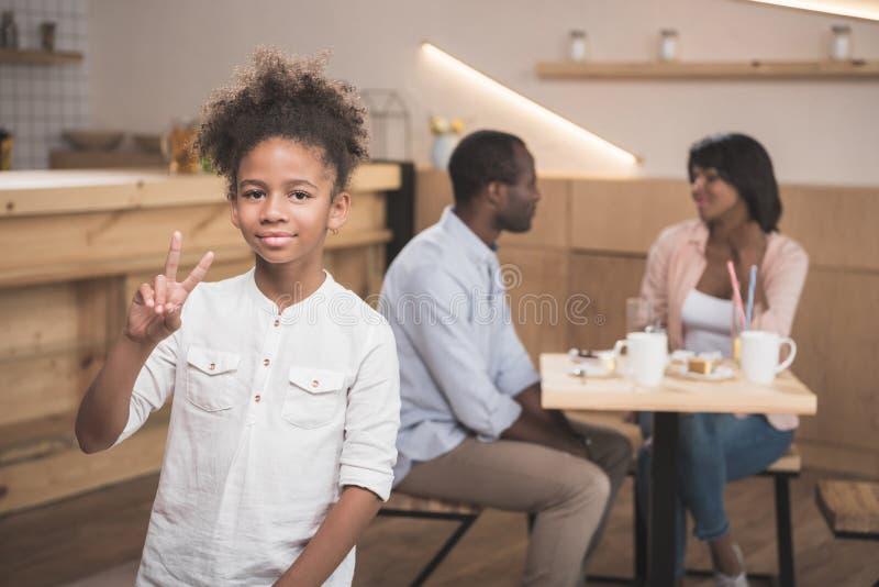 menina afro que mostra o sinal de paz com seus pais borrados fotos de stock