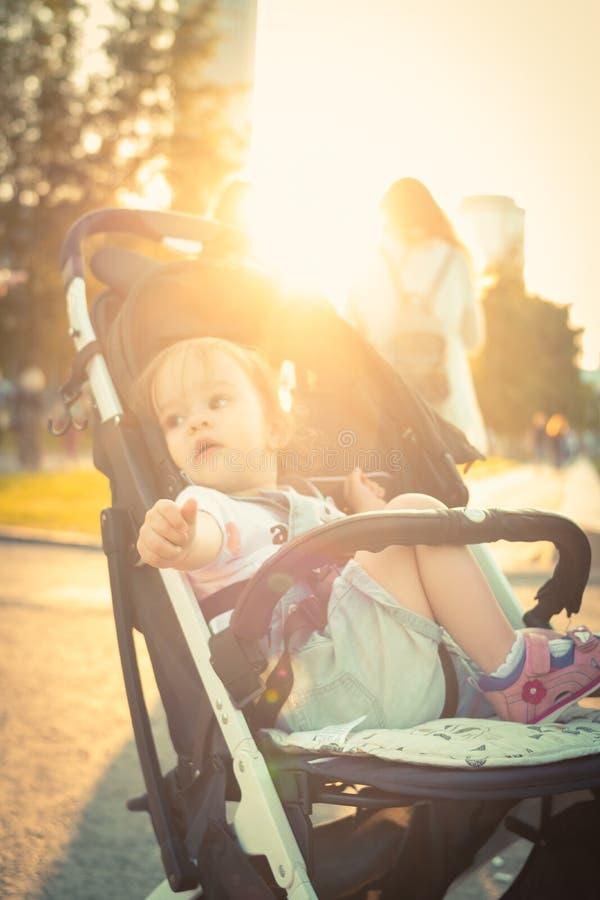 Menina agitada na vista curiosa do transporte de bebê ao redor foto de stock