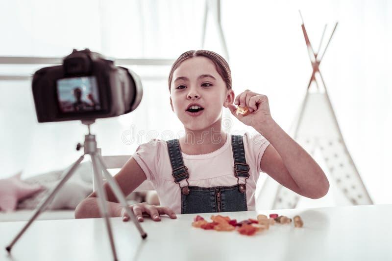 Menina agradável alegre que come doces na frente da câmera imagens de stock