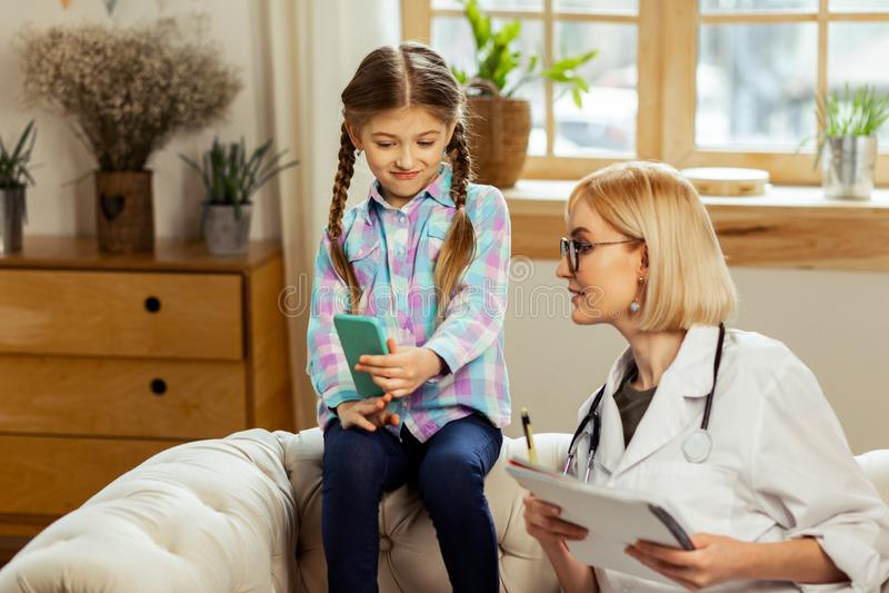 Menina agradável bonito que mostra a um médico fotos no telefone fotos de stock royalty free