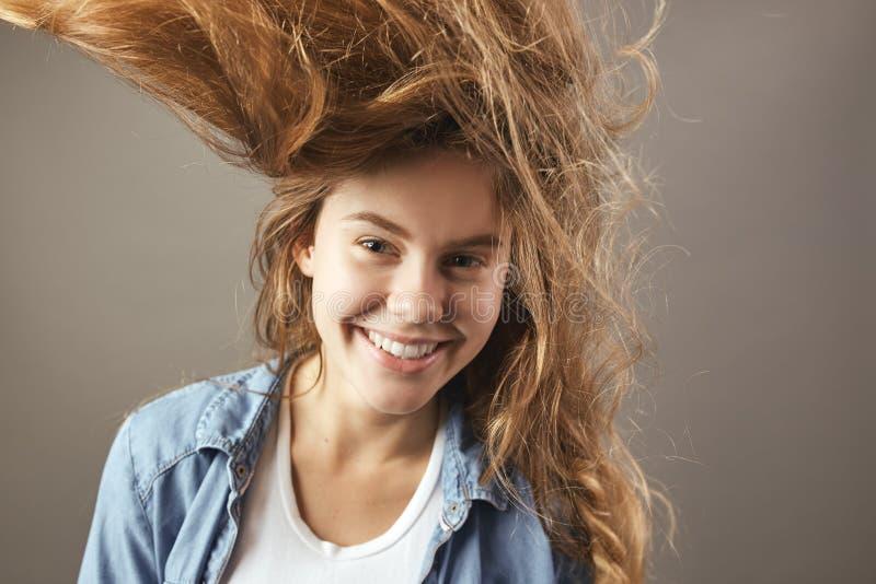 Menina agradável com sorrisos de fluxo marrons longos do cabelo em um fundo cinzento imagens de stock royalty free