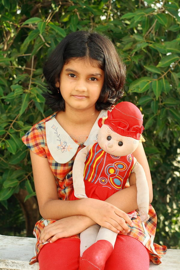 Menina agradável com sua boneca fotos de stock royalty free