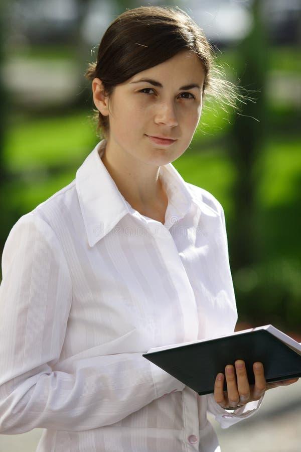 Menina agradável com um livro imagens de stock royalty free