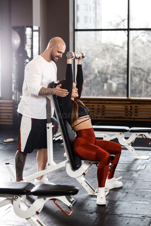 A menina agradável delgada faz uma imprensa de banco do peso acima do assento em um banco quando o homem atlético a segurar no gy foto de stock royalty free