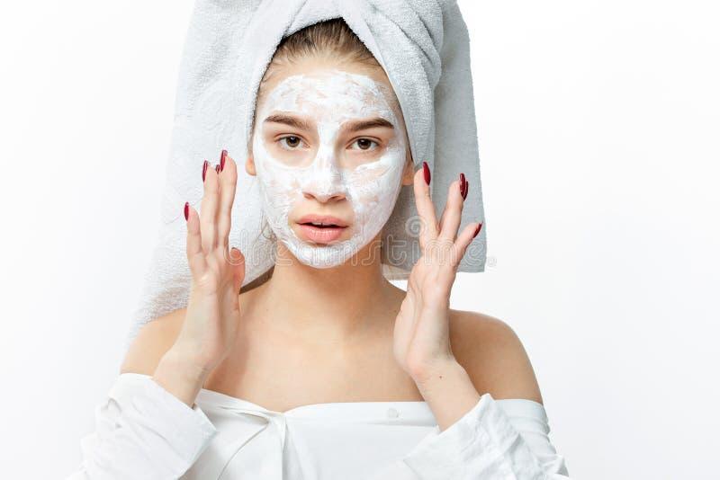 A menina agradável no a roupa branca com uma toalha branca em seu cabelo põe uma máscara cosmética sobre sua cara foto de stock