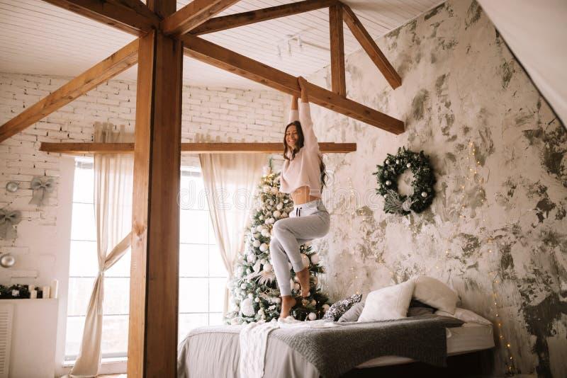 A menina agradável vestida na camiseta e nas calças brancas está pendurando em uma barra de madeira acima da cama com cobertura c fotografia de stock