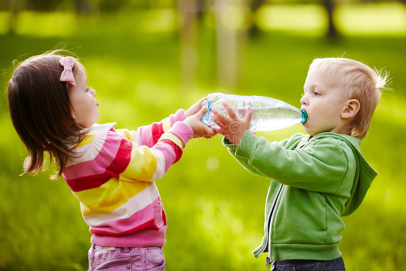A menina ajuda o menino a manter a garrafa imagem de stock