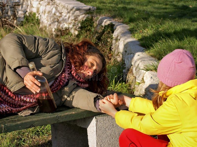 A menina ajuda uma mulher bêbedo imagem de stock