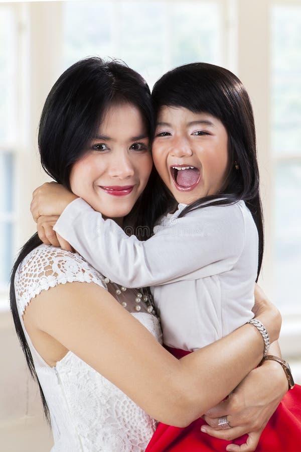 A menina alegre abraça sua mãe em casa fotografia de stock
