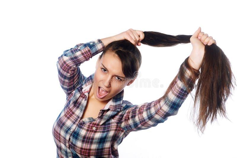 Menina alegre amusing que guarda seu cabelo longo no rabo de cavalo sobre o fundo branco imagens de stock