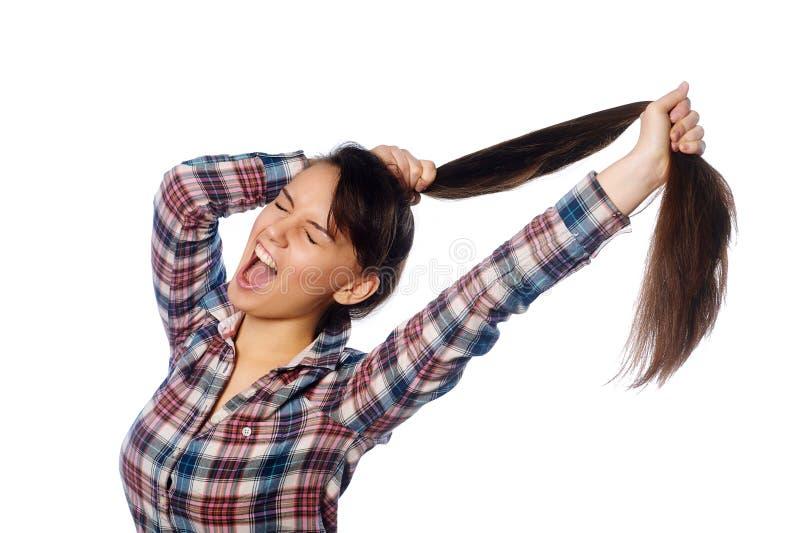 Menina alegre amusing que guarda seu cabelo longo no rabo de cavalo sobre o fundo branco imagem de stock royalty free