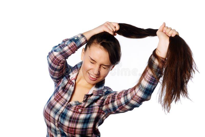Menina alegre amusing que guarda seu cabelo longo no rabo de cavalo sobre o fundo branco fotografia de stock royalty free
