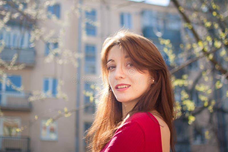 Menina alegre atrativa com sorriso saudável bonito e os bordos sensuais que aprecia a mola na cidade durante o dia ensolarado foto de stock