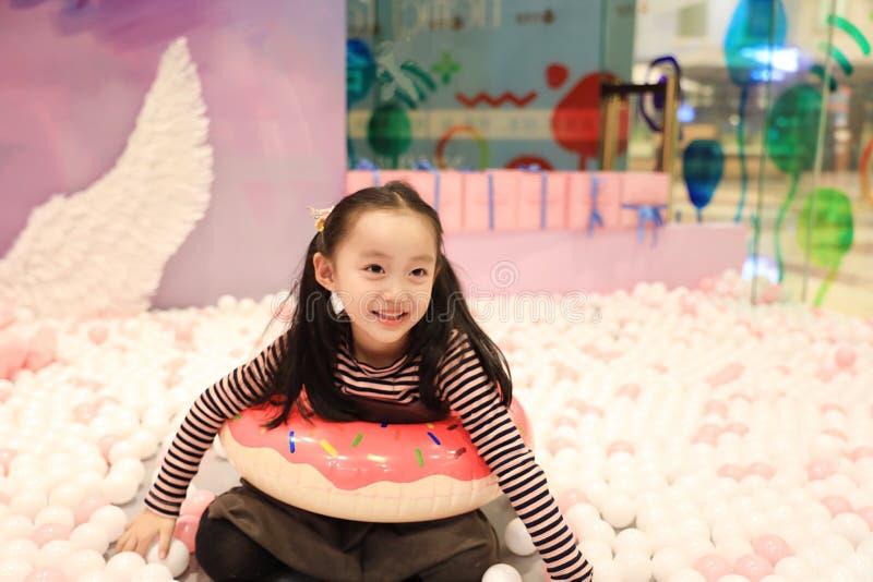 Menina alegre bonita que joga a terra de prazer no campo de jogos fotos de stock royalty free