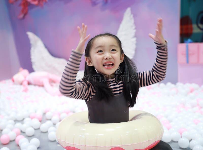 Menina alegre bonita que joga a terra de prazer no campo de jogos imagens de stock royalty free
