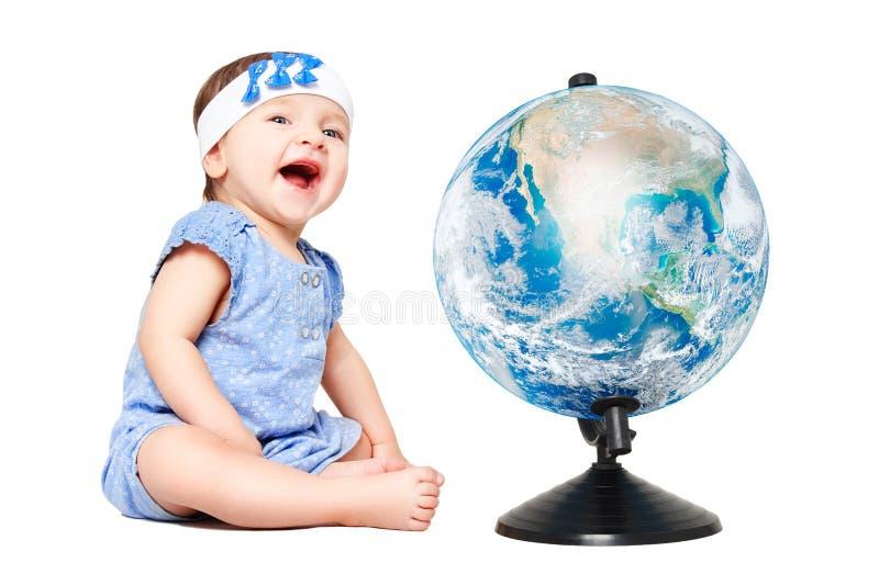 Menina alegre bonito que senta-se ao lado do globo do mundo fotografia de stock royalty free